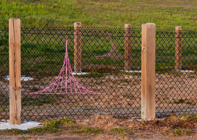 fence yarn bombed with string art