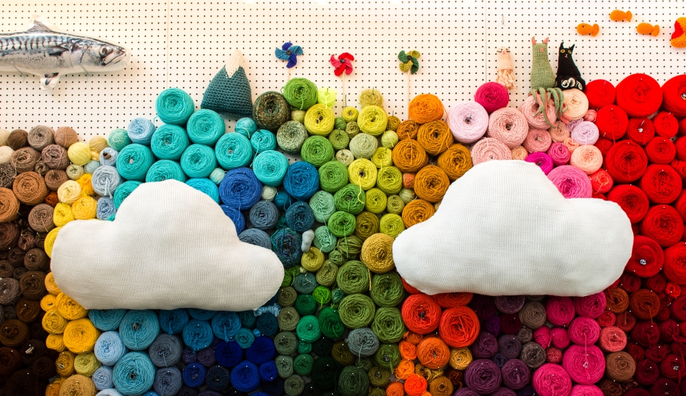 Machine knit clouds on a wall of yarn